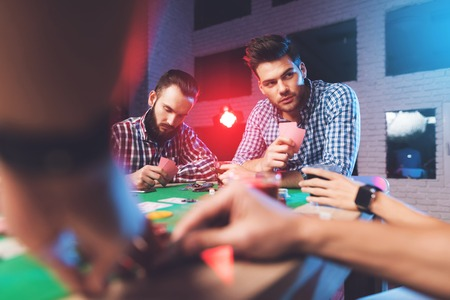 Young people play poker at the table. Banco de Imagens