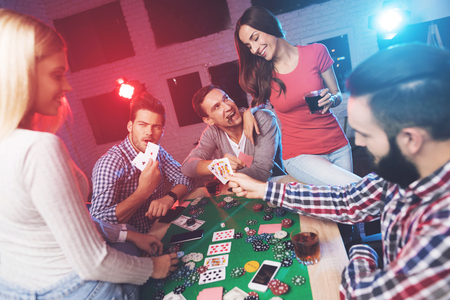 Young people play poker at the table. Stok Fotoğraf