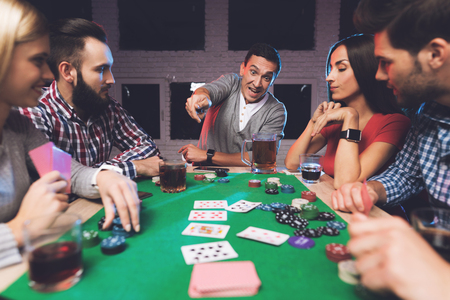 Young people play poker at the table. Фото со стока