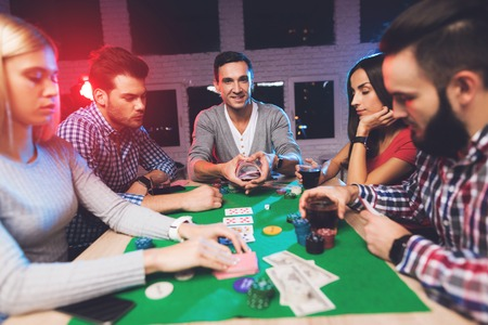 Jongeren spelen poker aan tafel. Stockfoto
