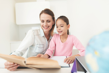 Mom helps my daughter do her homework in the kitchen.