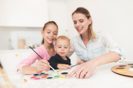 Mother and children are engaged in drawing. They have fun in the kitchen. The girl is holding her younger brother in her arms.