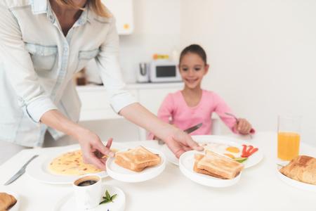 ママは、彼女の娘の朝食を与えます。彼らは、明るいキッチン。