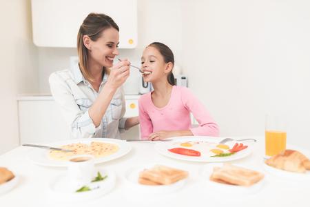 ママと娘は台所に座って朝食を食べている。彼らは朝食を楽しんでいます。