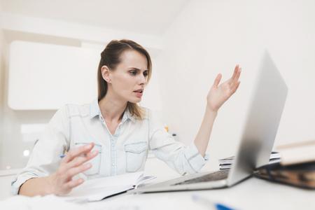 Een vrouw werkt thuis. Ze werkt op een laptop. Stockfoto