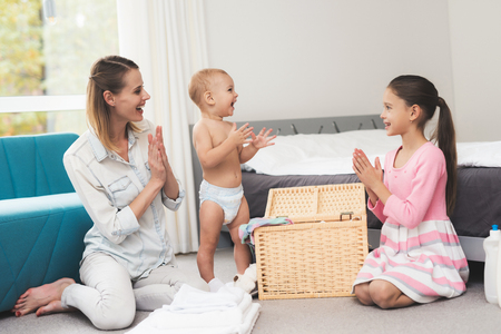 A mother of two children has fun with children during house cleaning. They are in a bright room and put clothes in their places Stock Photo