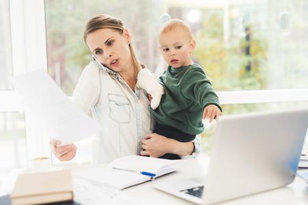 Kobieta pracuje na urlopie macierzyńskim w domu. Kobieta jednocześnie pracuje i opiekuje się dzieckiem. Zdjęcie Seryjne