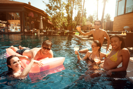 Friends swim in the pool with an inflatable mattress.