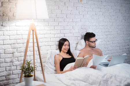 A guy is lying in bed and working on a laptop. The guy does not pay attention to his girlfriend.