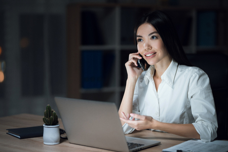 Girl is working late in the dark office with a laptop. Young beautiful businesswoman girl in office.