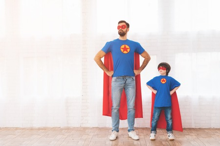 Father and son in the red and blue suits of superheroes. On their faces are masks and they are in raincoats. 스톡 콘텐츠