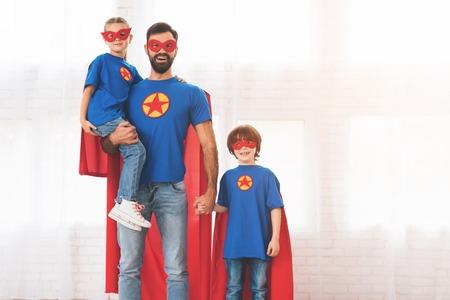 레드와 블루의 슈퍼 영웅들의 정장을 입은 아이들과 함께하는 아버지. 그들은 가면과 우비에서.