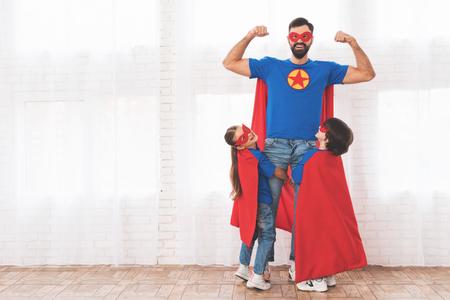 父亲带着孩子们穿着红蓝相间的超级英雄套装。他们戴着面具,穿着雨衣。