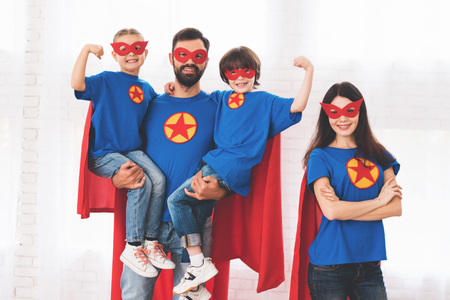 Young family in red and blue suits of superheroes. Their faces in masks and they are in raincoats.