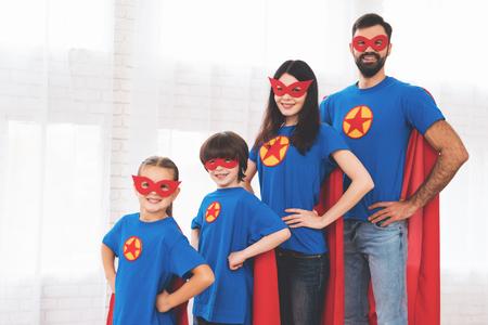 Młoda rodzina w czerwonych i niebieskich garniturach superbohaterów. Ich twarze w maskach i płaszczach przeciwdeszczowych.