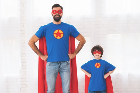 Father and son in the red and blue suits of superheroes. On their faces are masks and they are in raincoats. Banco de Imagens