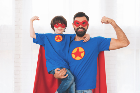 Father and son in the red and blue suits of superheroes. On their faces are masks and they are in raincoats. Stock Photo