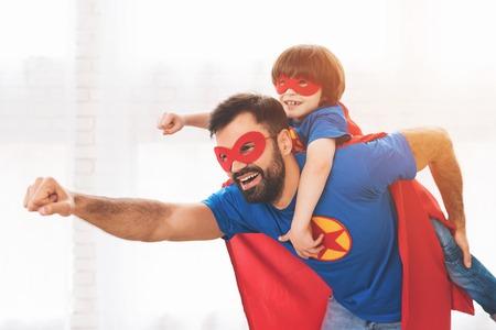Padre e hijo en los trajes rojos y azules de superhéroes. En sus rostros hay máscaras y llevan impermeables. Foto de archivo - 90801253