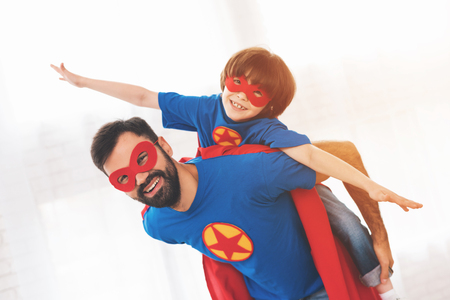 Father and son in the red and blue suits of superheroes. On their faces are masks and they are in raincoats. 版權商用圖片