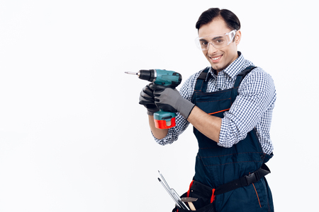 A man of Arab appearance works as a repairman. Handyman posing on white background.