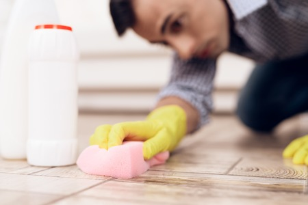 A man cleaning the floor in the apartment. Handyman is cleaning the apartment