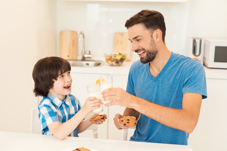 Father and son have breakfast in the light kitchen. Standard-Bild