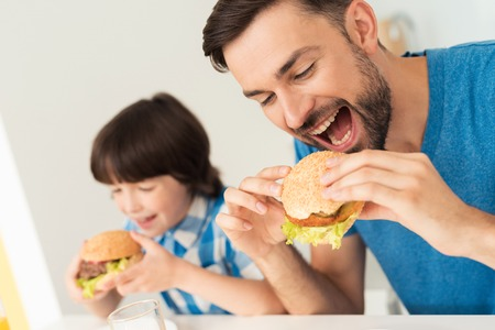 Father and son have breakfast in the light kitchen. Stockfoto