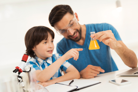 Father and son conduct chemical experiments at home. Standard-Bild