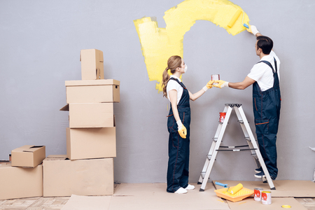 Young woman and a man of Arab appearance works as a painter. A woman and a man are painting walls.