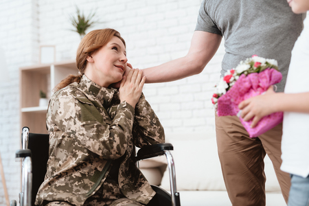 Woman veteran in wheelchair returned from army. The son and husband are happy to see her. Imagens - 97780118
