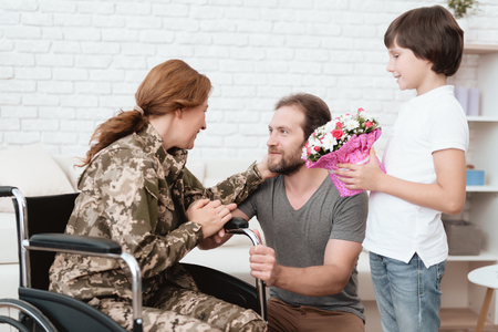 Woman veteran in wheelchair returned from army. The son and husband are happy to see her. Imagens - 97780120