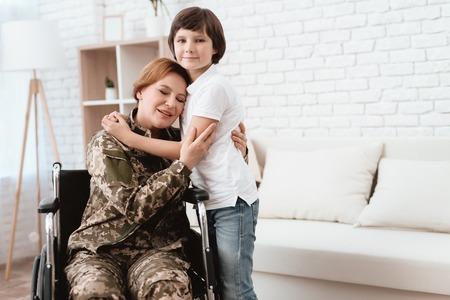 Woman veteran in wheelchair returned home. Son hugs mom in wheelchair.