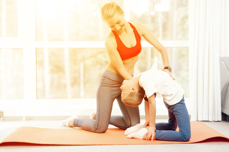 Mother and daughter are engaged in yoga in sportswear. They are in a bright room with panoramic windows.