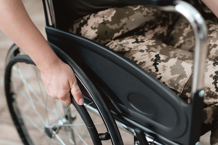 Woman veteran in wheelchair returned from army. Close-up photo veteran woman in a wheelchair. Wheelchairs and legs in military uniform.