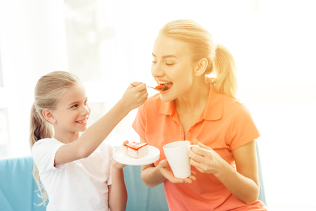 Mother and daughter are sitting on the couch in a bright room. They are eating a cake. Фото со стока