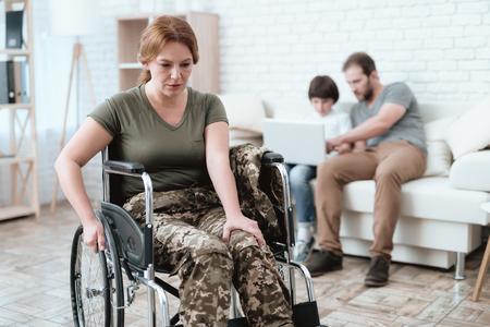 휠체어에 여자 베테랑 군대에서 반환합니다. 휠체어에 여자 고통입니다. 군복을 입은 체스. 스톡 콘텐츠