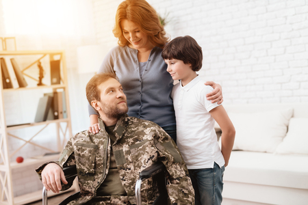 The veteran in a wheelchair came back from the army. A man in uniform in a wheelchair with his family.