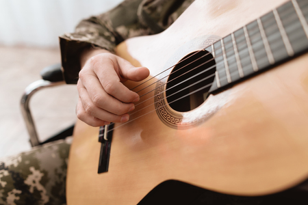 A veteran in a wheelchair is playing the guitar. Close-up photo of guitar and hands. A man in military uniform. Stock Photo