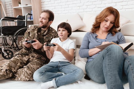 The family spends time together. A disabled father in military uniform is playing with his son on console.