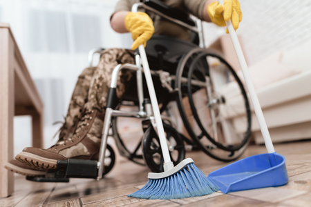 A female veteran in a wheelchair is cleaning the house. She's in military uniform. A woman in yellow gloves sweep of dust.Her family is busy with ordinary business.
