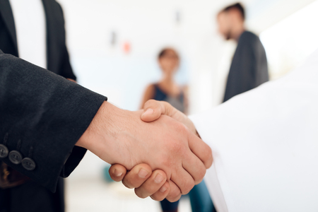 A man in arabian clothes and a man in a business suit are shaking hands. Stockfoto