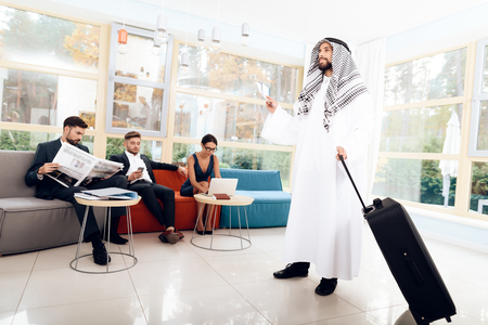 A man in arabian clothes is holding a suitcase.
