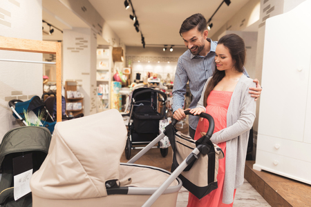 A pregnant woman together with a man choose a baby carriage. Foto de archivo