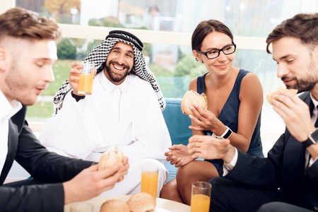 A man in arabian clothes and other businessmen are sitting at a table with burgers and juice.