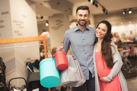 A pregnant woman and a man are posing for a camera with goods in a shopping center.