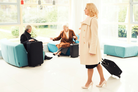 Elderly couple in the airport lounge. They are in the waiting room with suitcases.