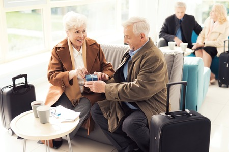 Elderly couple in the airport lounge. An elderly man makes an unexpected gift to an elderly woman.