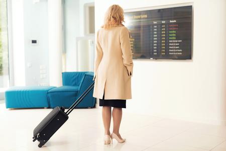 Een vrouw staat bij de dienstregeling op de luchthaven. Een vrouw houdt een koffer.