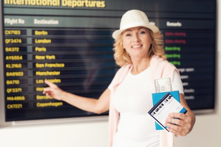 Elderly woman at the airport posing for a photo. She has a timetable against the background.