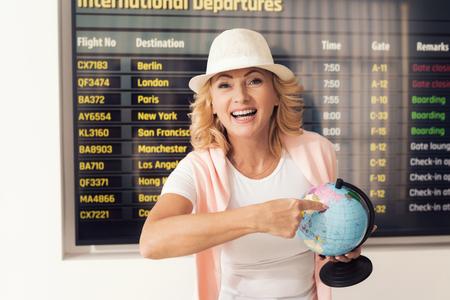 Bejaarde op luchthaven het stellen voor een foto. Ze heeft een tijdschema tegen de achtergrond. Stockfoto - 91096277